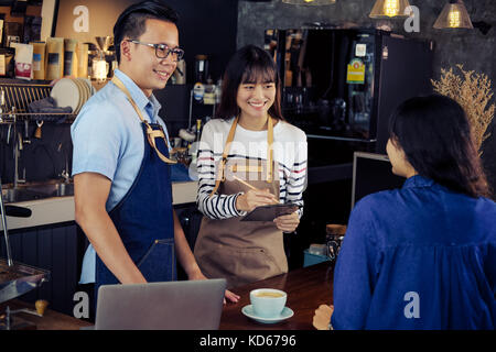Young asian baristas ordering at counter bar in cafe. Cafe restaurant service, food and drink industry concept. - Stock Photo