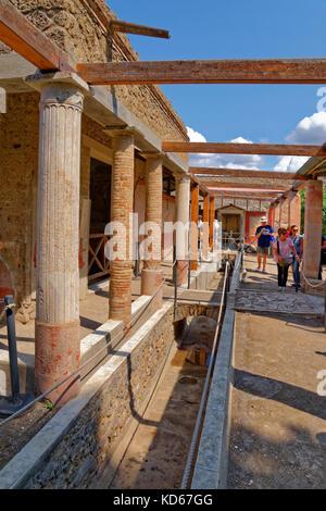 Water course & exterior of the Octavius Quarto house at the ruined Roman city of Pompeii at Pompei Scavi, near Naples, - Stock Photo