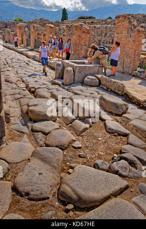 Street with communal water font in the ruined Roman city of Pompeii at Pompei Scavi, near Naples, Southern Italy. - Stock Photo