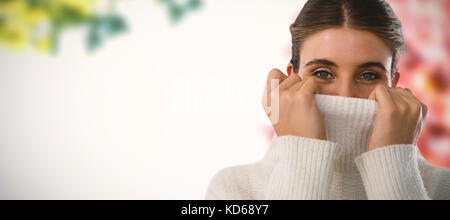 Portrait of young woman covering face with turtleneck sweater against view of maple leaves - Stock Photo