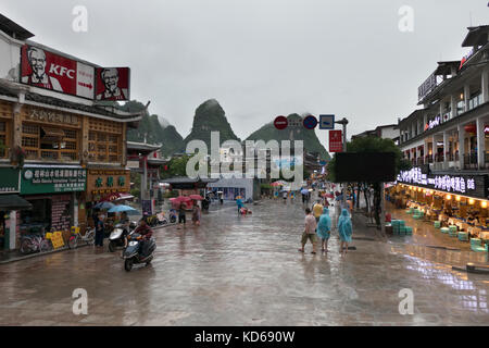 People and Chinese tourists shopping and walking in West Street of Yangshuo, China, Asia. Urban life with shops, - Stock Photo