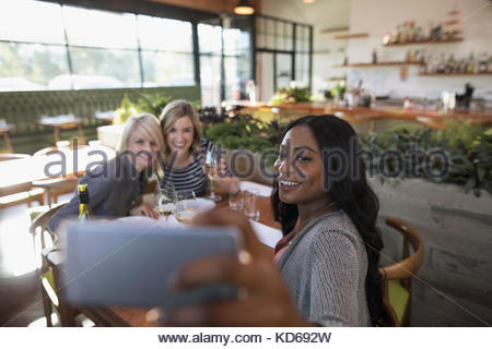 Smiling women friends taking selfie with camera phone, dining at restaurant table - Stock Photo