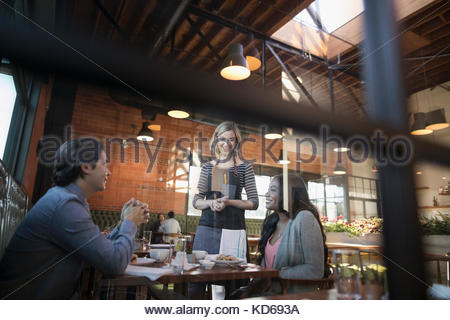 Female server serving food to couple at restaurant table - Stock Photo