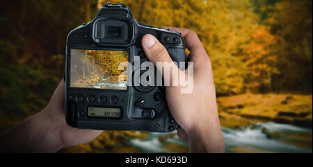 Cropped image of hands holding camera  against autumn scene - Stock Photo