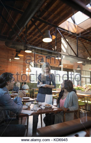 Female server taking order from couple at restaurant table - Stock Photo