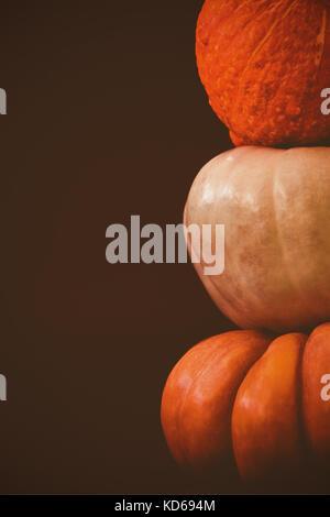 Stack of fresh pumpkins arranged against black background - Stock Photo