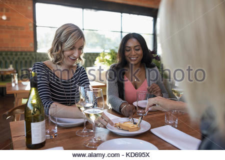 Women friends sharing dessert and drinking white wine, dining at restaurant table - Stock Photo