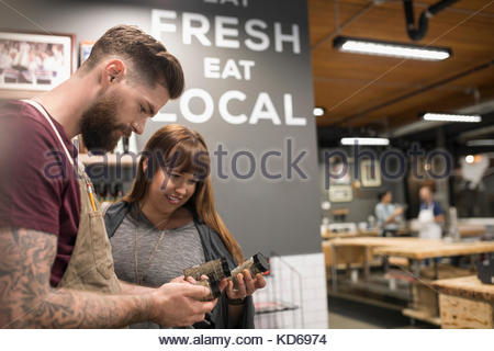 Butcher helping customer select spice rub in butcher - Stock Photo