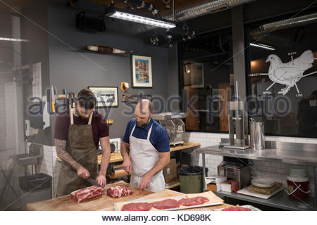 Male butchers cutting raw red meat in butcher - Stock Photo