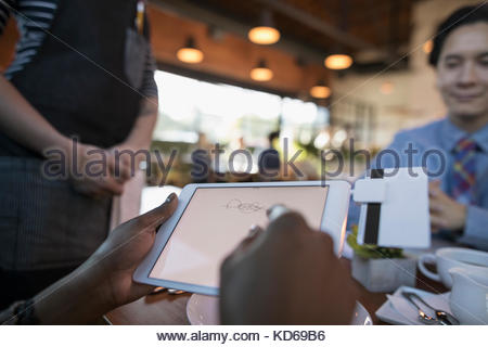 Female customer paying, signing digital tablet credit card swiper at restaurant table - Stock Photo
