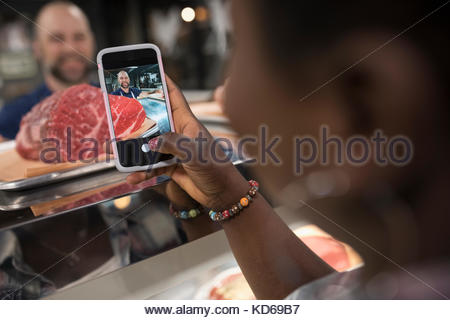 Customer with camera phone photographing raw red meat in butcher - Stock Photo