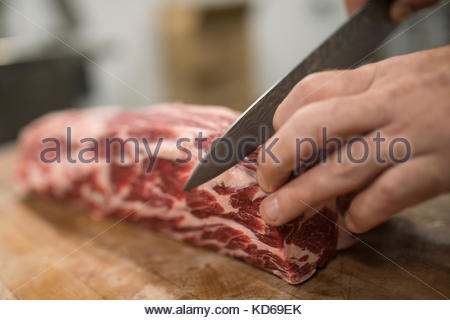 Close up butcher with knife cutting into marbled raw red meat in butcher - Stock Photo