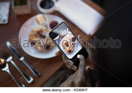Personal perspective woman with camera phone photographing food, dining at restaurant table - Stock Photo