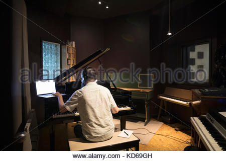 Male pianist playing grand piano, writing music at laptop in recording studio - Stock Photo