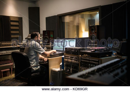 Male music producer working at computer in recording studio - Stock Photo