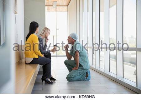 Attentive surgeon and doctor consoling woman in hospital - Stock Photo