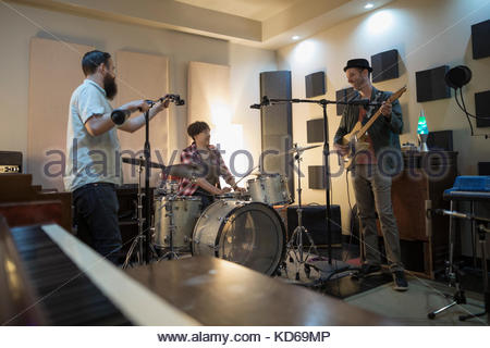 Musicians playing in recording studio - Stock Photo