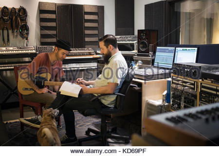 Male music producer and guitarist meeting in recording studio - Stock Photo