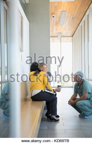 Attentive surgeon and doctor consoling, hugging woman in hospital - Stock Photo