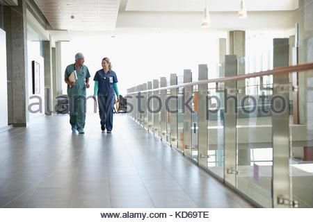Surgeon and nurse walking and talking in hospital corridor - Stock Photo