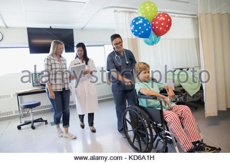 Doctor talking to mother and nurse pushing boy patient in wheelchair in hospital - Stock Photo