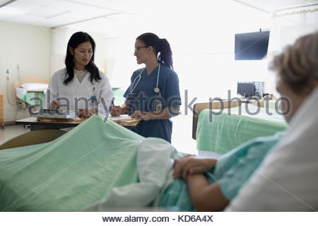 Female doctor and nurse making rounds, discussing medical record of boy patient in hospital - Stock Photo