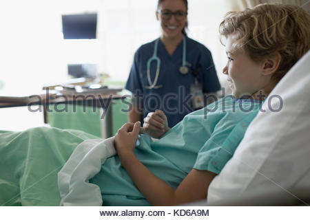 Female nurse smiling at boy patient in hospital bed - Stock Photo