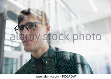 Confident, pensive brunette businessman in eyeglasses looking away - Stock Photo