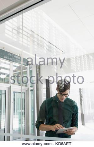 Brunette businessman using digital tablet in office lobby - Stock Photo