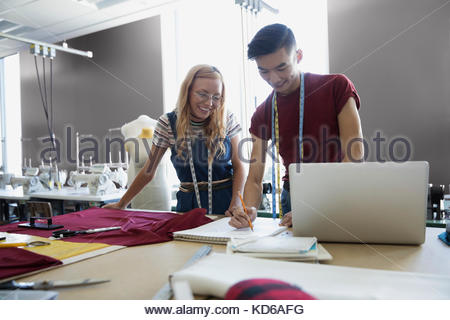Smiling fashion design students sketching at workbench in studio - Stock Photo
