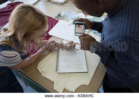 Fashion designers sketching and using camera phone at workbench in studio - Stock Photo