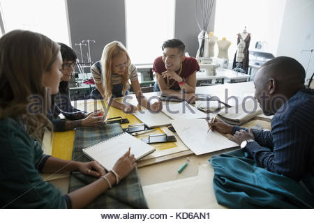 Fashion design students talking, sketching at workbench in studio - Stock Photo