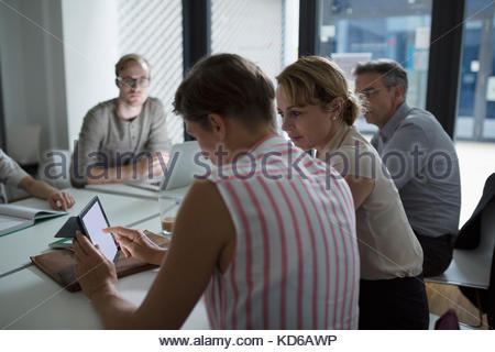 Businesswomen using digital tablet in conference room meeting - Stock Photo