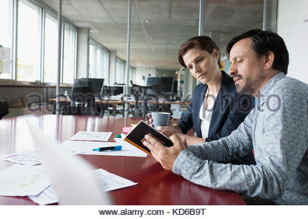Business people reviewing paperwork and notes in conference room meeting - Stock Photo