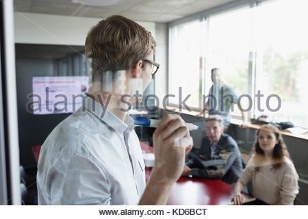 Businessman leading meeting, writing on glass in conference room - Stock Photo