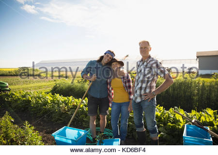 Portrait smiling, confident family farmers working in vegetable crop on sunny farm - Stock Photo