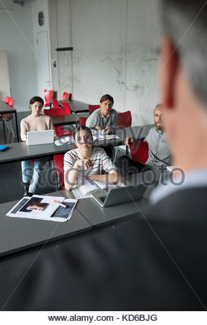Mature students listening to professor teaching lesson in classroom - Stock Photo