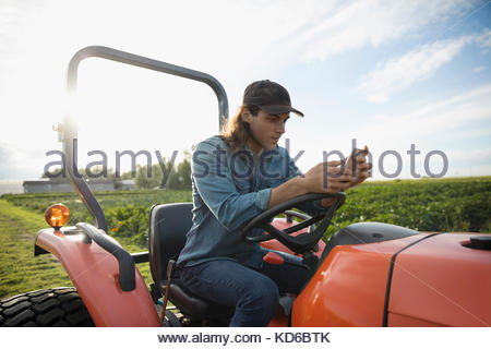 Male farmer texting with cell phone on tractor on sunny farm - Stock Photo