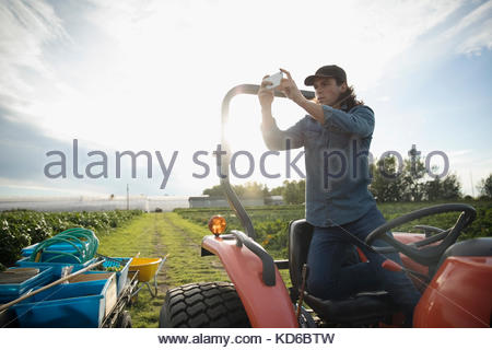 Male farmer photographing with camera phone on tractor on sunny farm - Stock Photo