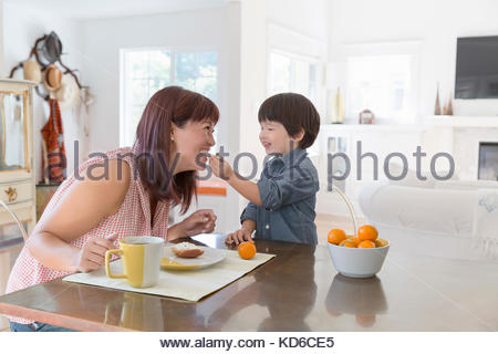 Playful son feeding mother at dining table - Stock Photo