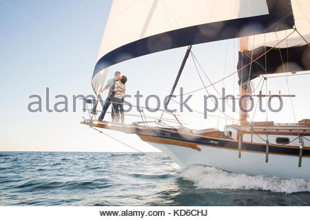 Affectionate couple kissing on sailboat on sunny ocean - Stock Photo