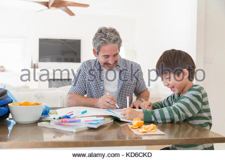 Father and son coloring with markers at dining table - Stock Photo