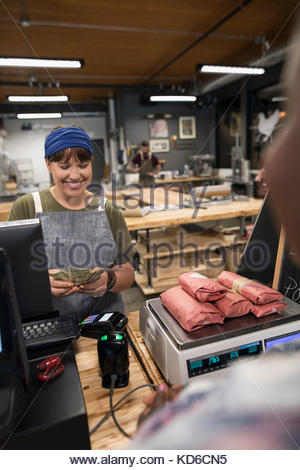 Female butcher counting cash payment from customer in butcher - Stock Photo