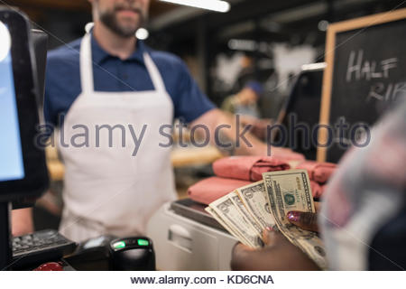 Customer with cash paying butcher in butcher - Stock Photo
