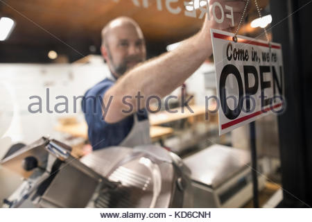 Male butcher changing open sign in butcher shop window - Stock Photo