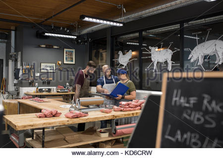 Butchers discussing paperwork in butcher - Stock Photo