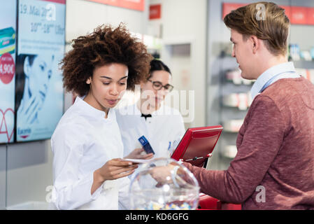 pharmacist selling prescribed medicines to a customer in a moder - Stock Photo