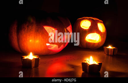 Scary halloween pumpkin and melon jack-o-lanterns on black background lit with small round and star candles. Selective - Stock Photo