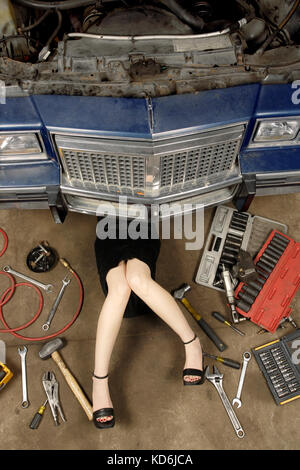 Photo of a woman wearing a black skirt and heels doing repairs under the front of an old car from the early 80's. - Stock Photo
