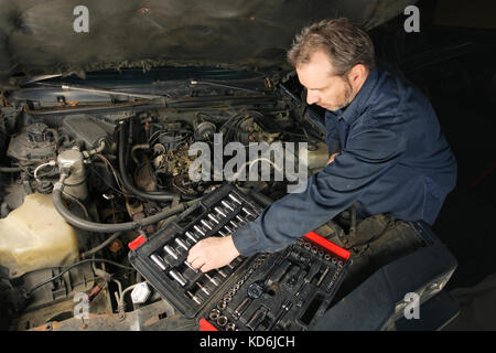 Photo of a mechanic repairing an engine of an old car. - Stock Photo